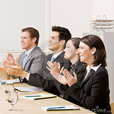 Co-workers applauding in meeting