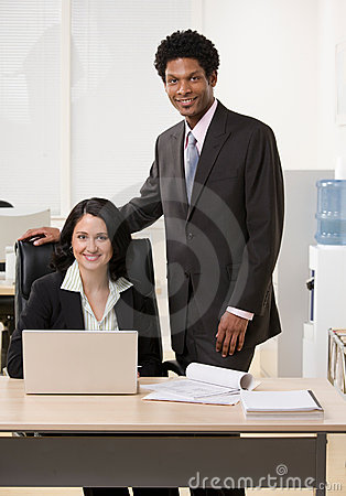 Co-workers with laptop at desk