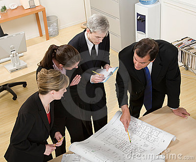 Co-workers reviewing blueprints