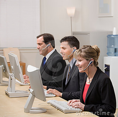 Co-workers working at computers in call center