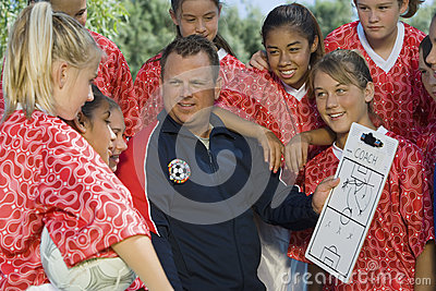 Coach Discussing Strategy With Girls Soccer Team