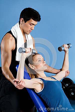 Coach helps woman to exercise with weights