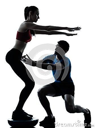 Coach man woman exercising squats on bosu