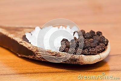 Coarse salt and pepper corns on wooden spoon
