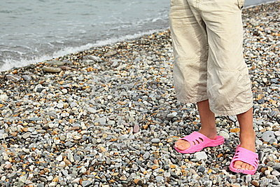 Coast of sea. legs of child with slippers