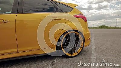 Coche amarillo-naranja en el estacionamiento, neum?ticos discretos de los deportes E r 05 almacen de video