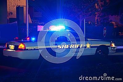 Coche del sheriff en la noche con las luces encendido