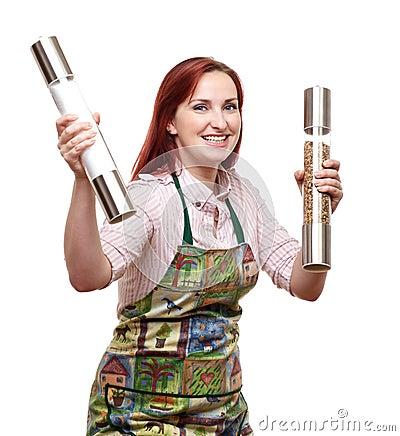 Cocinero de la mujer que sostiene molinos de la sal y de pimienta