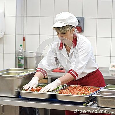 Cocinero de sexo femenino que hace la ensalada