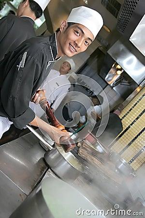 Cocinero que cocina en la cena