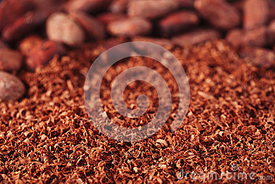 Cocoa beans and grated chocolate background, shallow dof