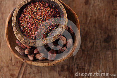 Cocoa beans and grated dark chocolate in old texured spoons bowl