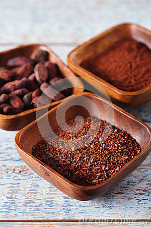 Cocoa beans, powder and grated chocolate in wooden bowls