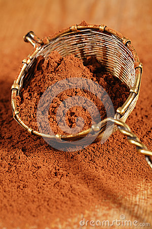 Cocoa powder in old rustic style silver sieve