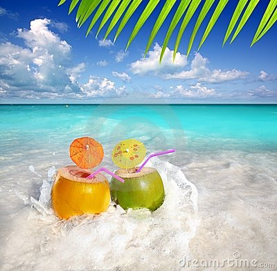 Coconut cocktails in tropical beach water splash
