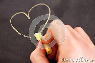 Coeur femelle de retrait de main sur le tableau noir
