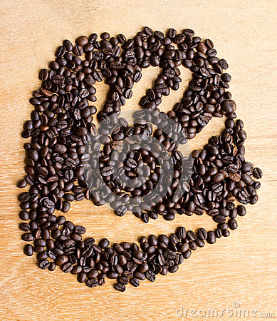 Coffee beans arranged in a hand on  wooden floor.