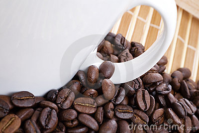Coffee beans and cup on bamboo