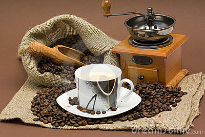 Coffee beans, cup of coffee and grinder