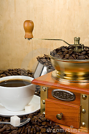 Coffee beans, cup and grinder on wood