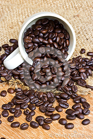 Coffee beans and cup on wood background