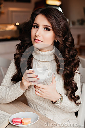 Free Coffee. Beautiful Girl Drinking Tea Or Coffee. Cup Of Hot Beverage. Brunette In A Cafe Drinking Tea, Eating Sweets Stock Images - 69256484