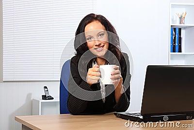 Coffee break for beautiful woman at office desk