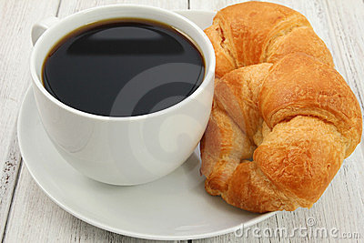 Coffee and croissants on white wooden background