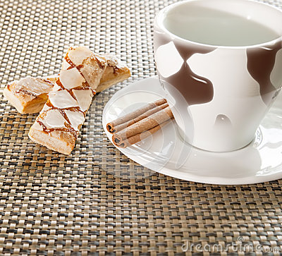 Coffee cup, cinnamon, sweets on the background