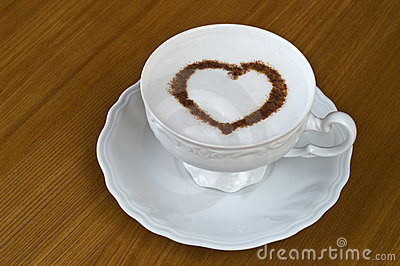Coffee cup with heart on table