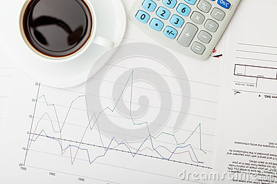 Coffee cup over some financial documents - view from top