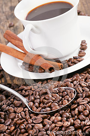 Coffee cup surrounded by coffee beans and scoop.