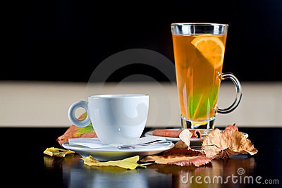 Coffee cup and tea glass next to autumn leaves