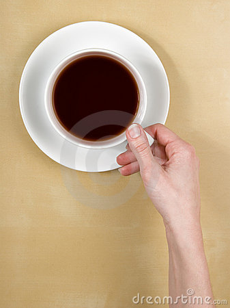 Coffee -female hand holds a cup of tea on table