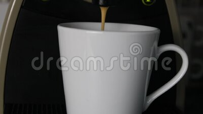 Coffee flowing in a cup. Coffee maker and cup detail video stock footage