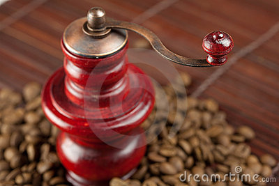Coffee grinder and coffee beans on a bamboo mat