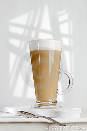 Coffee latte with frothy milk in tall glass