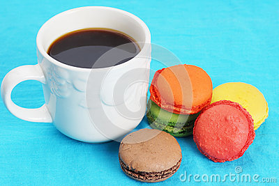 Coffee and macarons on blue