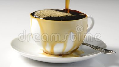 Coffee overflowing the cup. Coffee pouring into a cup and overflowing indicating absent mindedness stock video