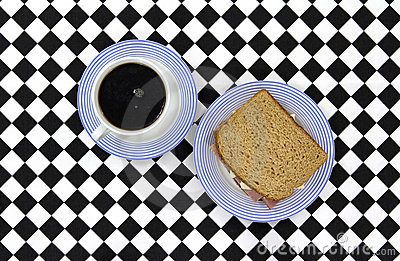 Coffee and sandwich on checkerboard tablecloth