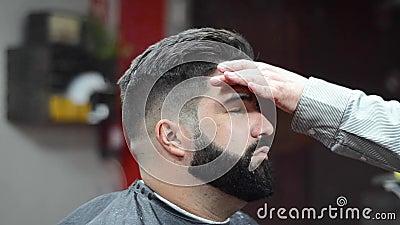 Coiffeur employant la coiffure de fixation de laque au salon de coiffure banque de vidéos