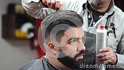 Coiffeur employant la coiffure de fixation de laque au salon de coiffure clips vidéos