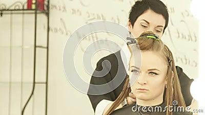 Coiffeur féminin à l'aide de la bride pour les cheveux de réparation pendant la coiffure dans le salon de beauté Fermez-vous vers banque de vidéos