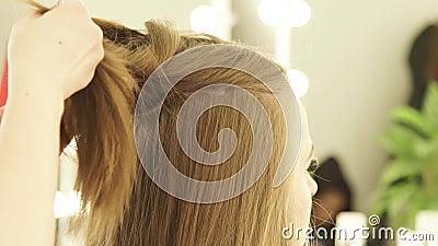 Coiffeur fixant de longs cheveux avec la bride pour le hairstyling dans le salon de coiffure Fermez-vous vers le haut du coiffeur banque de vidéos