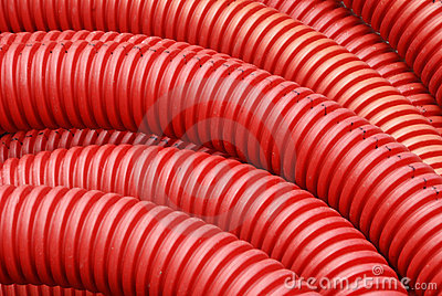 Coil of red plastic corrugated plumbing pipe