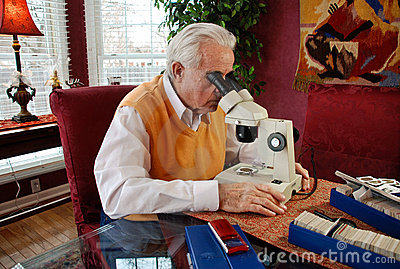 man viewing old coin under a microscope