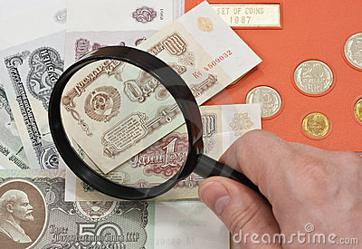 Coins with collector s hand and magnifying glass