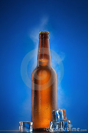 Cold beer bottle with drops on blue