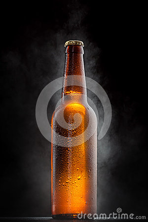 Cold beer bottle with drops on black