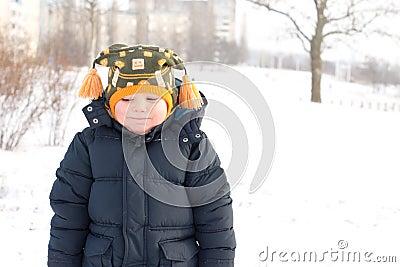 Cold little boy in winter snow